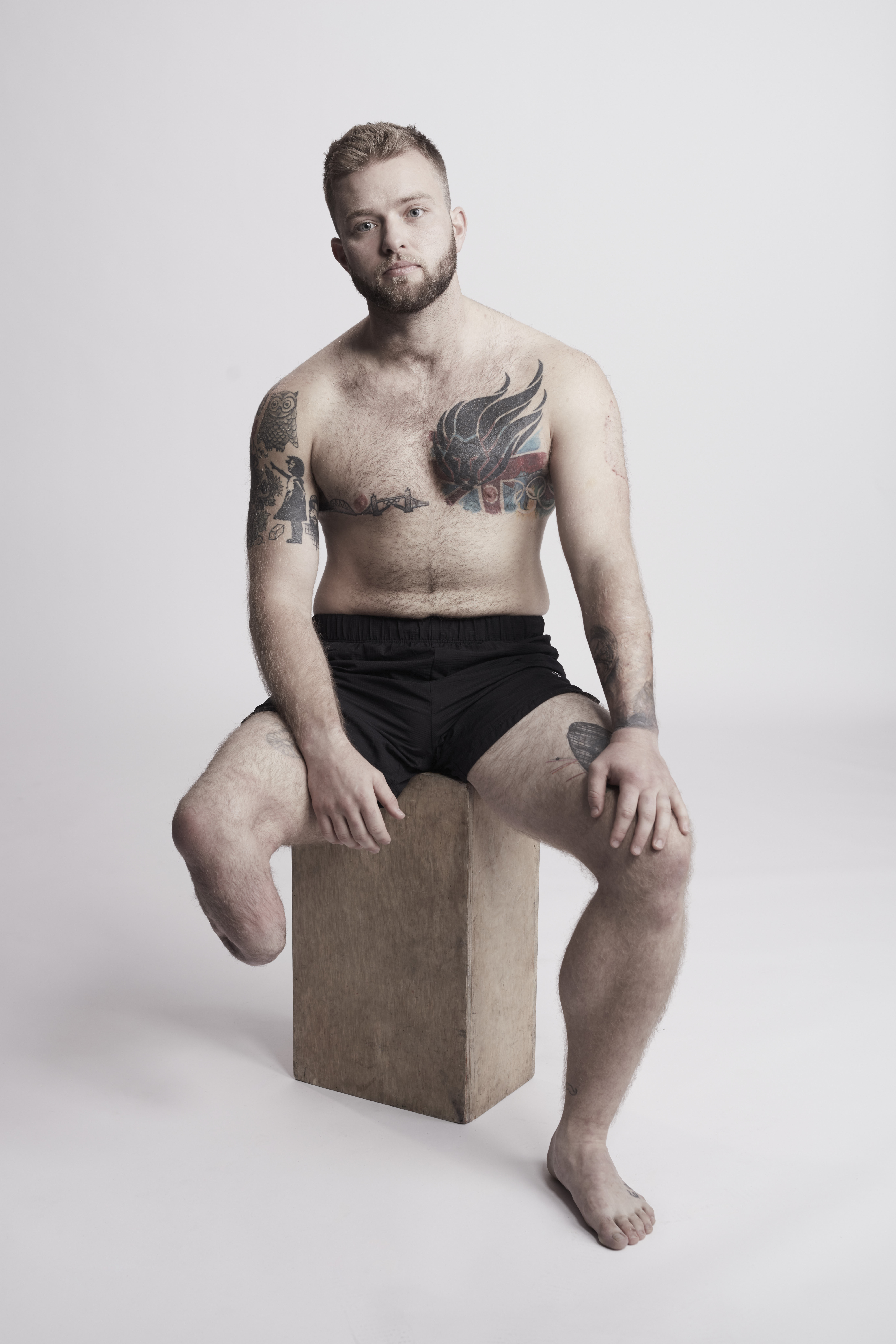 Jamie, a man with lower limb amputation and tattoos sitting on a wooden stool.