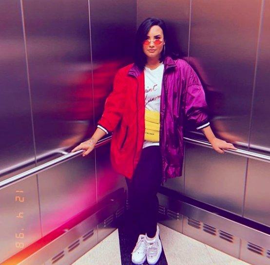 Demi Lovato posing in the corner of an elevator