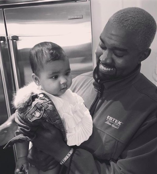 Black and white image of Kanye West holding his daughter
